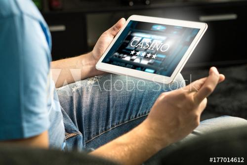 Excited man playing in an online casino with tablet fingers crossed wishing and hoping to win. Slot machine app. Person holding smart mobile device in hand at home.